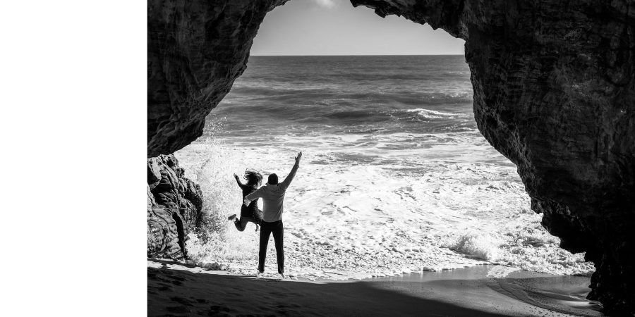 B&W jumping under the natural bridge as waves come in - Panther Beach Santa Cruz and Quail Hollow Felton engagement photography - Sara and Scott - photos by Bay Area wedding photographer Chris Schmauch